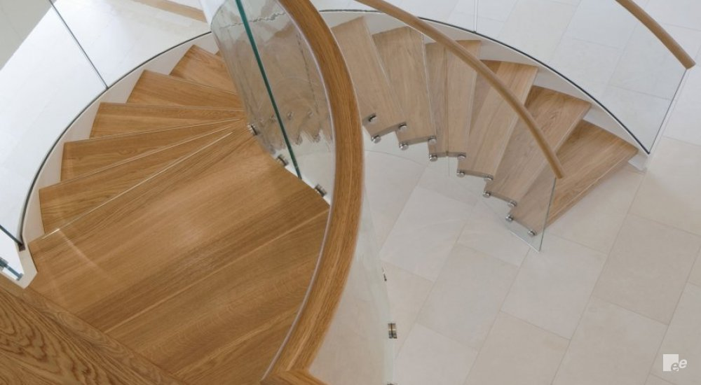 An oaken floor and floating staircase with oaken treads, above a natural stone floor and wooden plinths.