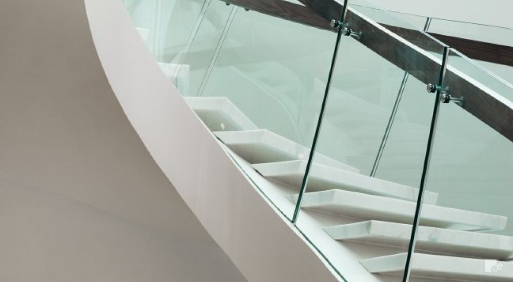 Glass balustrades with knotty wood staircase railings, along a winding staircase with natural stone treads in front of a white stucco wall.