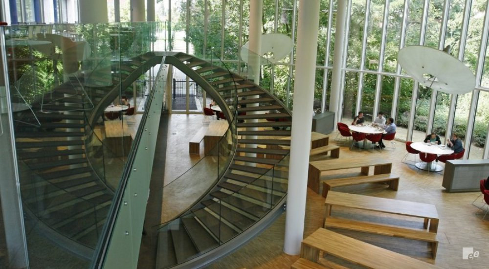 A space with lots of windows, with a wooden floor and wooden benches and tables. A large spiral staircase with glass railings.
