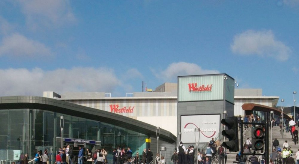 The entry of the Westfield Stratford shopping centre in London, with people on stairs and clouds above.