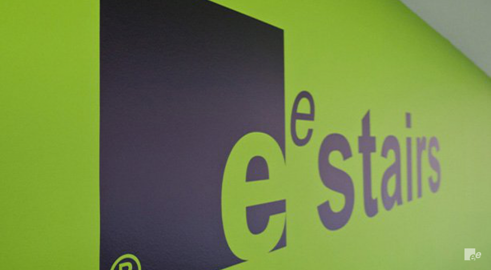 Black letters on a lime green background form the logo of EeStairs in the offices in London.