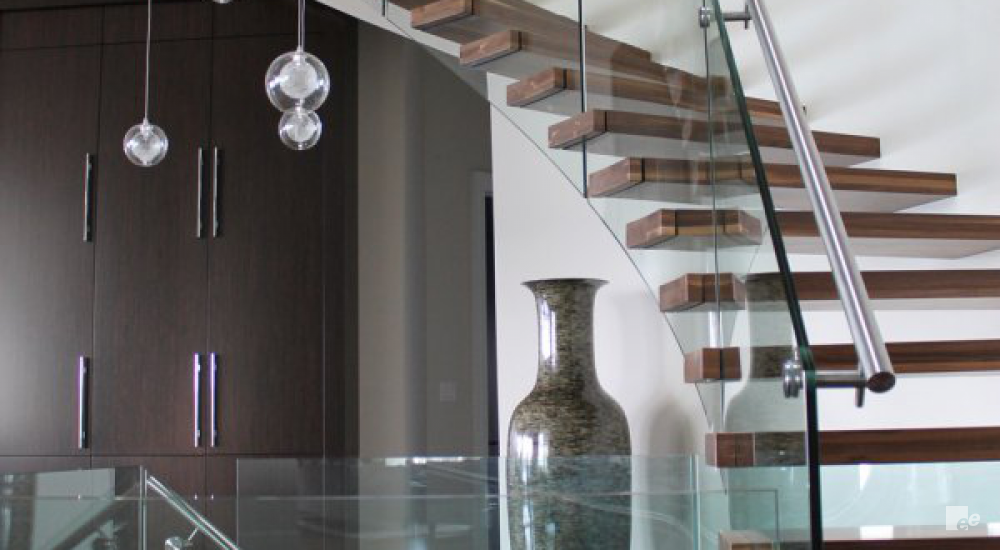A natural stone vase, hanging lamps, a white stucco wall and a floating staircase with walnut wood treads.