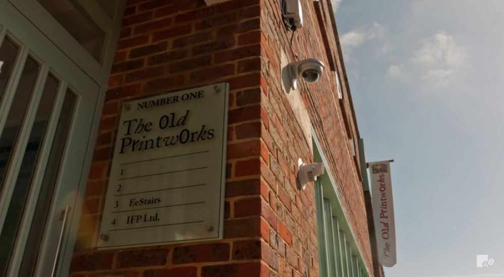 The brick wall, door, camera and the name sign at entrance of The Old Print Works.