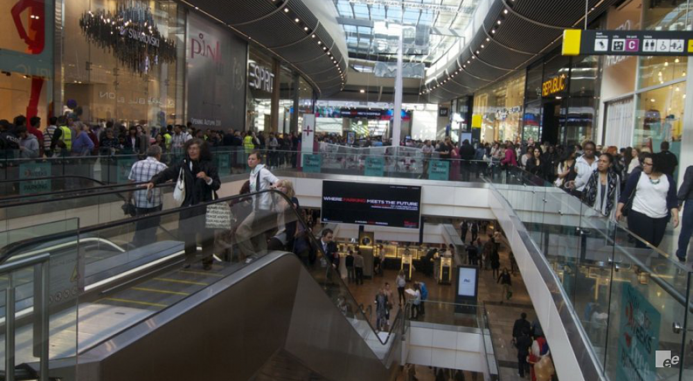A glass roof, stages, the shopping public and an escalator in the Westfield Stratford shopping centre in London.
