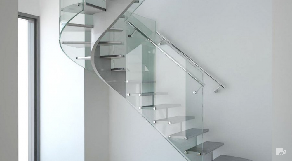 A staircase with natural stone treads and glass balustrade by a window in an apartment in New York.