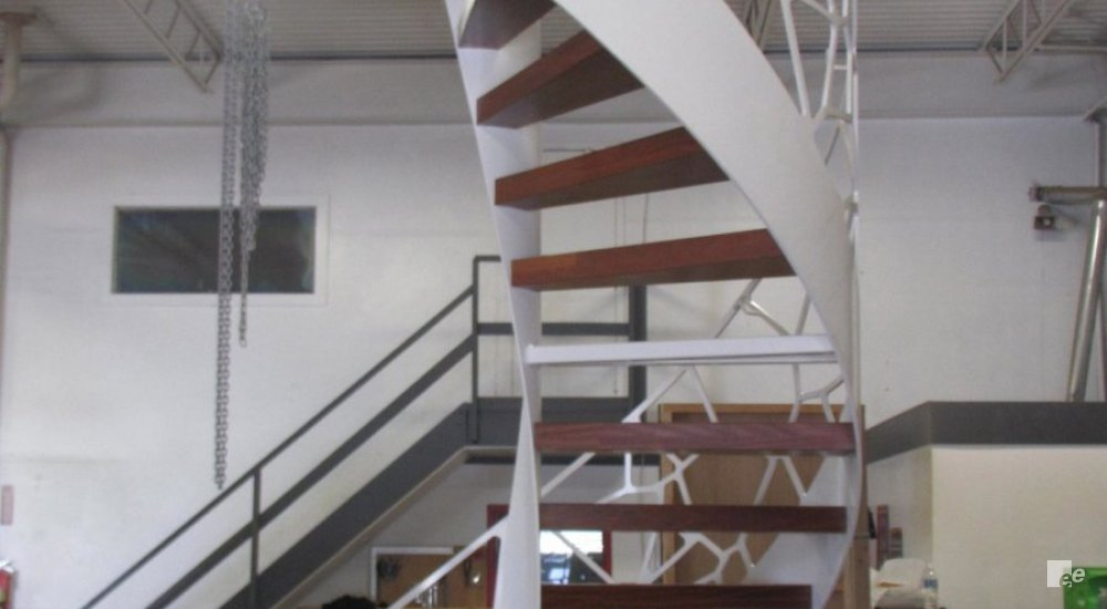 A staircase in a workplace with ceiling lamps, a flight of stairs and a person at a screen.