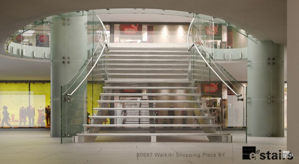 An open staircase with glass balustrades and stainless steel handrails in a shopping centre in Honolulu in Hawaii.
