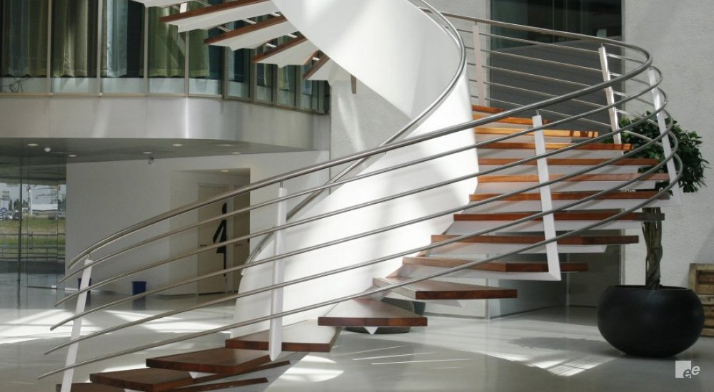 A winding staircase with floating treads and stainless steel balustrade in a hall with cast floor and dark plant pot.