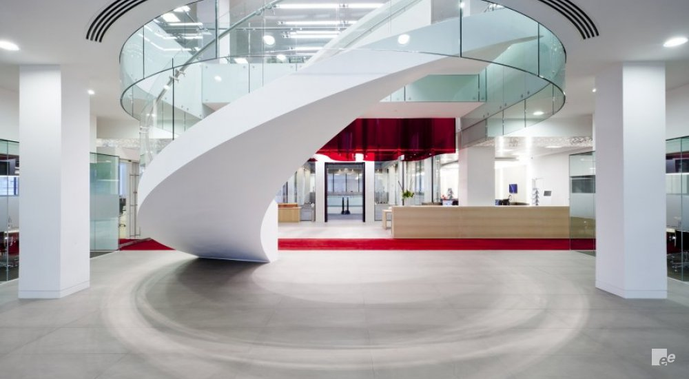 A winding staircase with glass balustrade in a hall with red carpet, concrete floor and wooden bins.