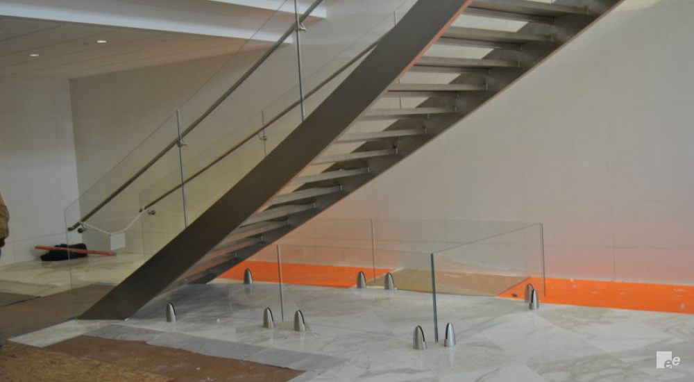 A staircase with stainless steel staircase pillars, next to a white stucco wall and above a natural stone floor and carpet tiles.