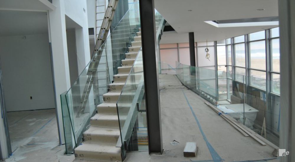A flight of stairs with glass balustrades, next to a steel crossbeam in a summer residence on the Atlantic Ocean.