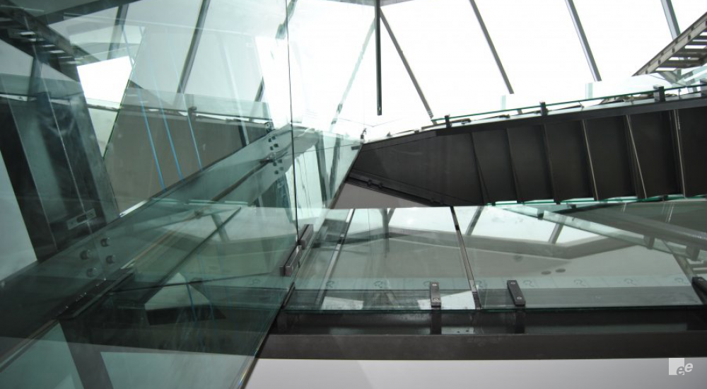 A glass lift shaft and glass balcony under a glass roof in a summer residence on the Atlantic Ocean.