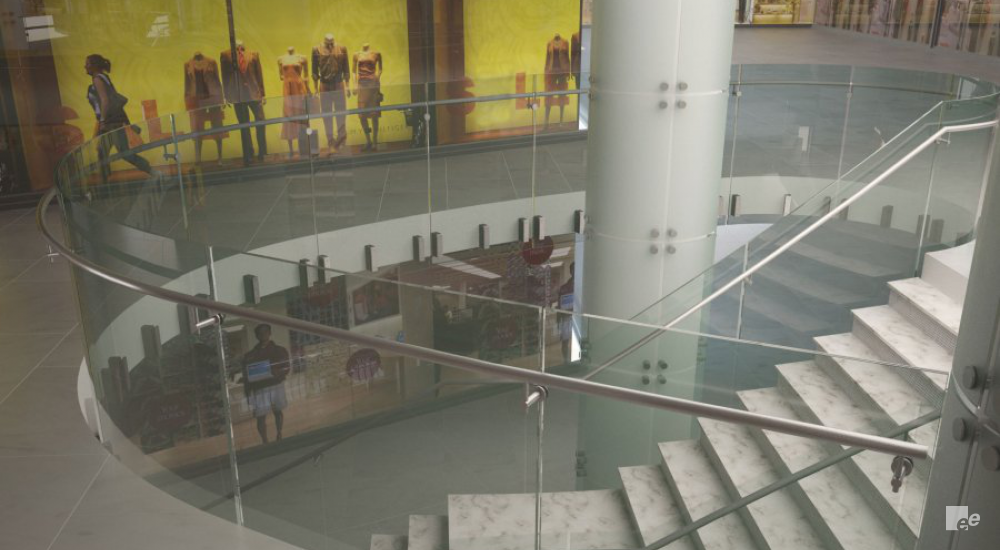 An open staircase with marble treads, in front of a column and glass walls with illustrations of people.