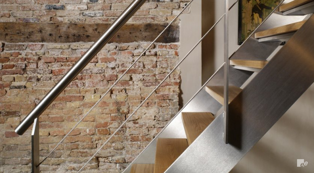A brushed stainless steel staircase with wooden treads and tension wires in front of a rough brick wall.