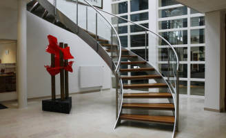 A winding staircase with balustrade in a hall with a marble floor, glass façade, radiator and artwork.
