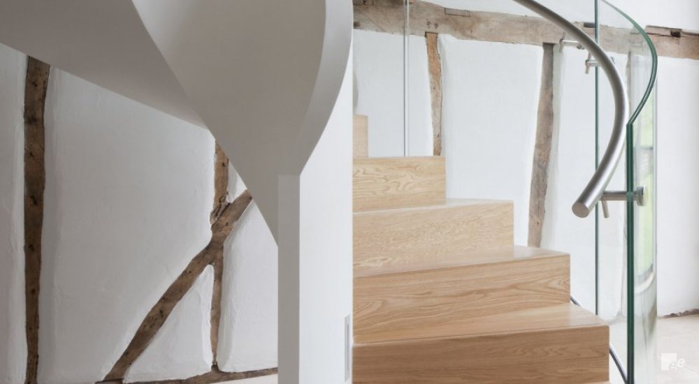A staircase with glass balustrade and oaken treads in a 300-year-old shed with oaken frame.