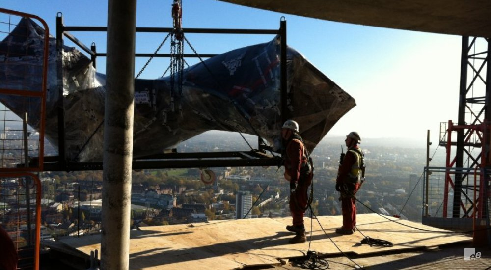 Two construction workers guide the placement of a winding staircase in a penthouse with a view of London.