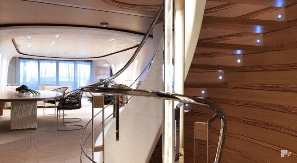 The interior of luxury yacht MS Northlander with a staircase, balustrade, ceiling lighting and table and chairs.