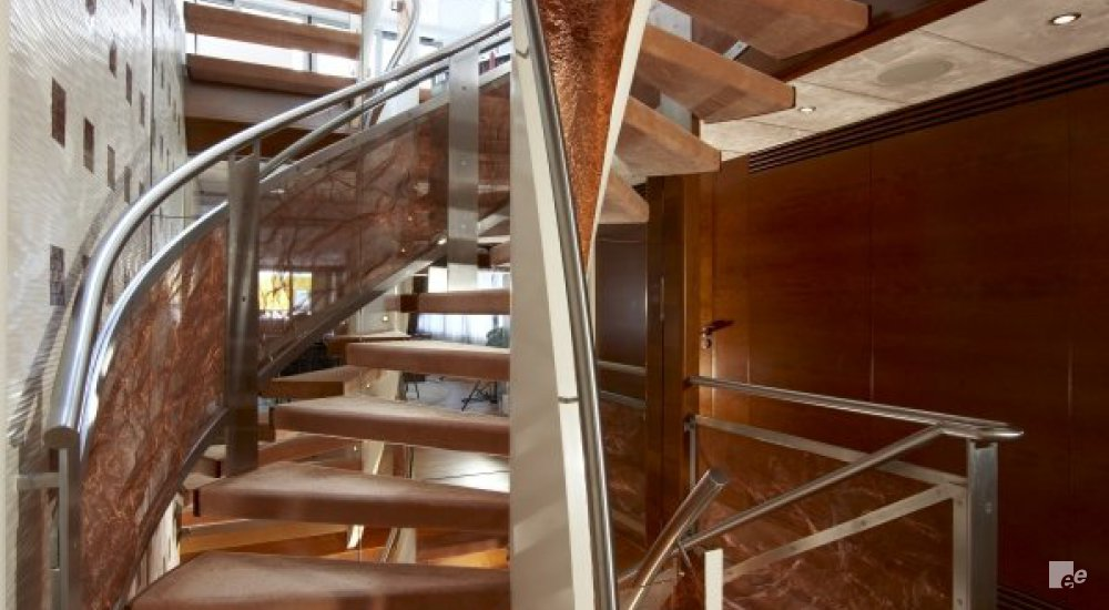 A wooden winding staircase in luxury yacht MS Sofia, next to a wall with LED lighting and under ceiling lighting.