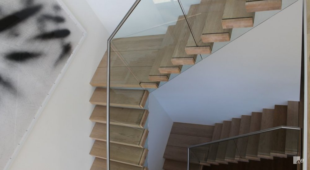 A double floating staircase in a white stucco hall. A photo frame is also partially visible.