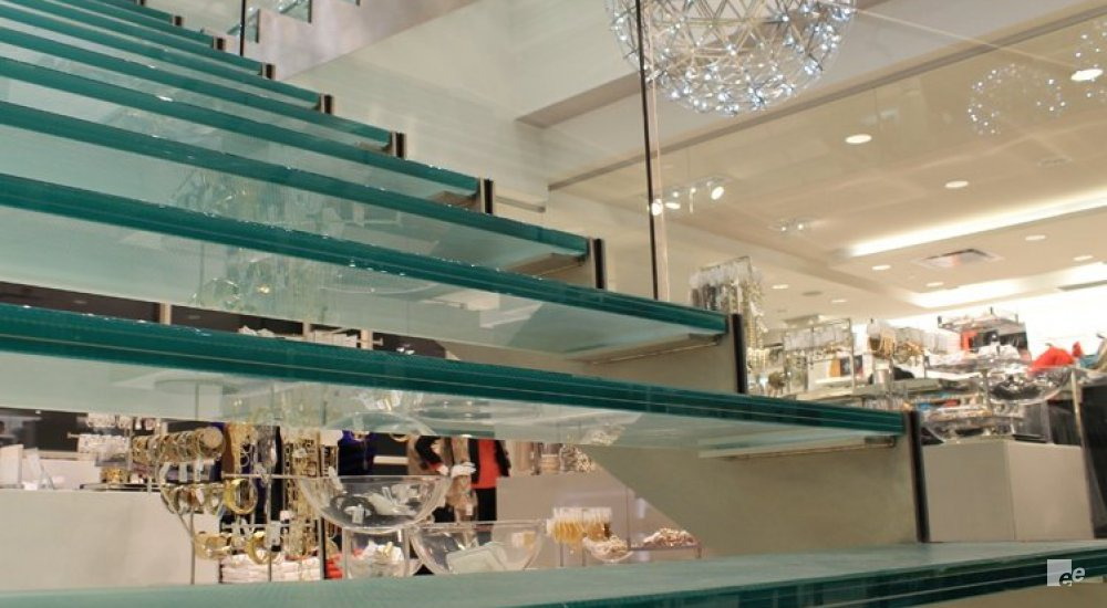 Glass staircase treads in a hall with ceiling lighting and a hanging lamp in the shape of a bird's nest.