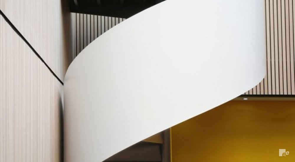 The thick balustrade of a winding staircase, next to a wooden wall and in front of a yellow stucco wall.