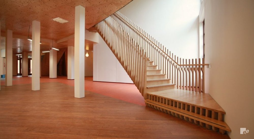 A bamboo staircase with landings, in a room with parquet floor, pillars and a ceiling with wood motif.