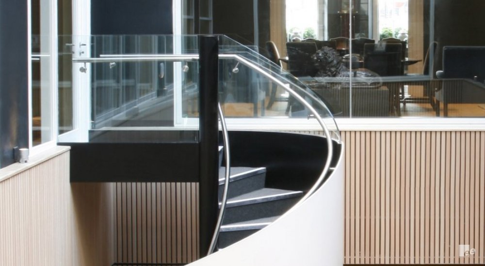 The winding staircase in the law offices of Brown Rudnick's Mayfair, with a view of an office space through a window frame.