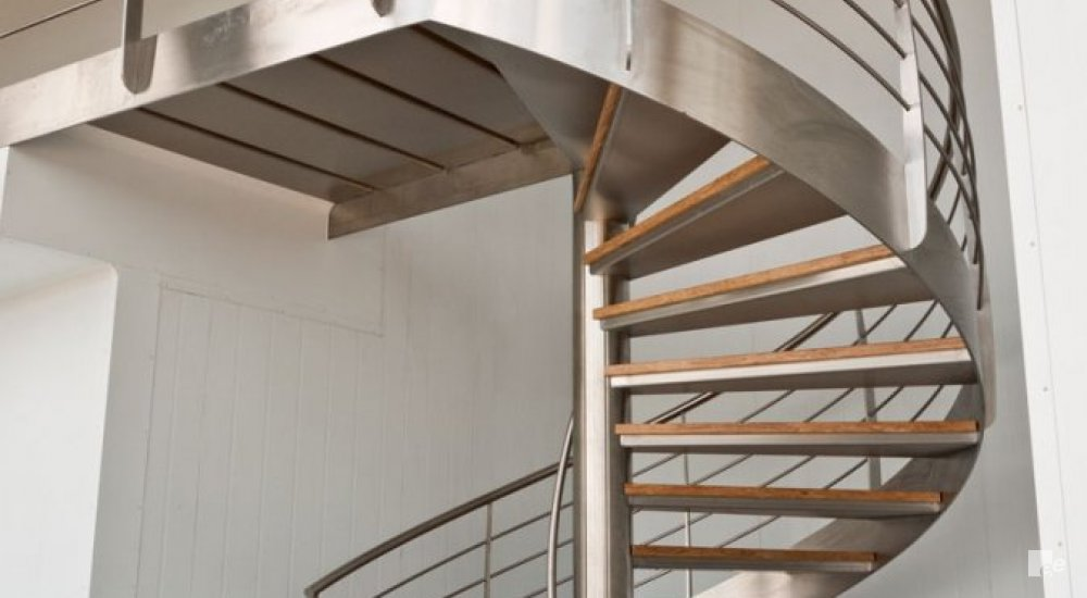 An open spiral staircase with bamboo treads and stainless steel balustrade in the building of Kanes Foods in England.