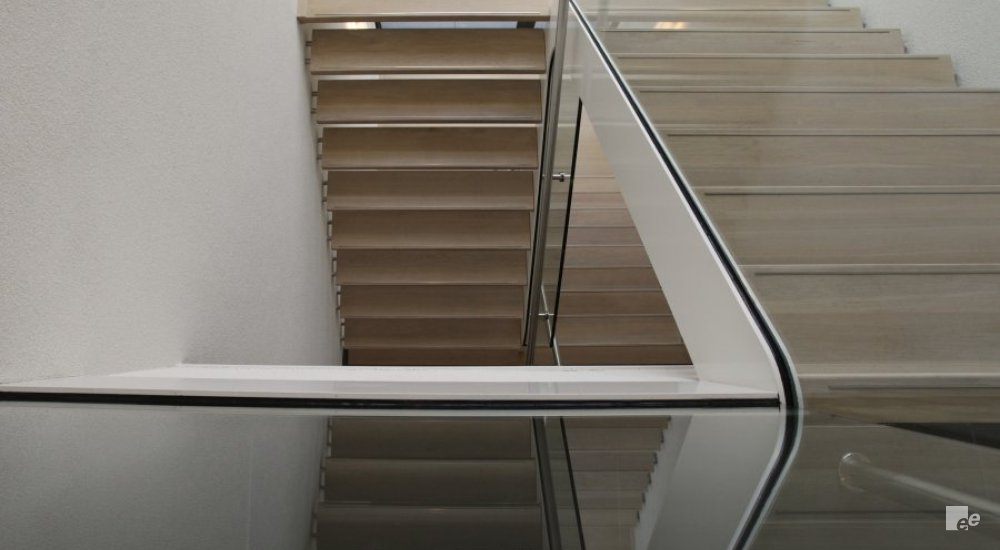 A glass balustrade reflects a wooden staircase with landing and a white stucco wall.