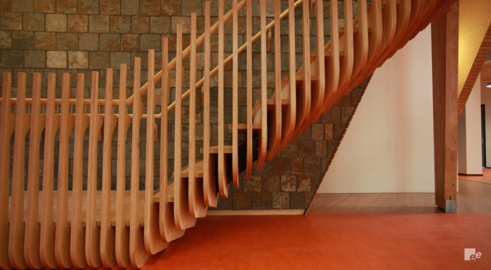 A bamboo staircase with bamboo balustrades, in front of a brick wall and above a linoleum floor.