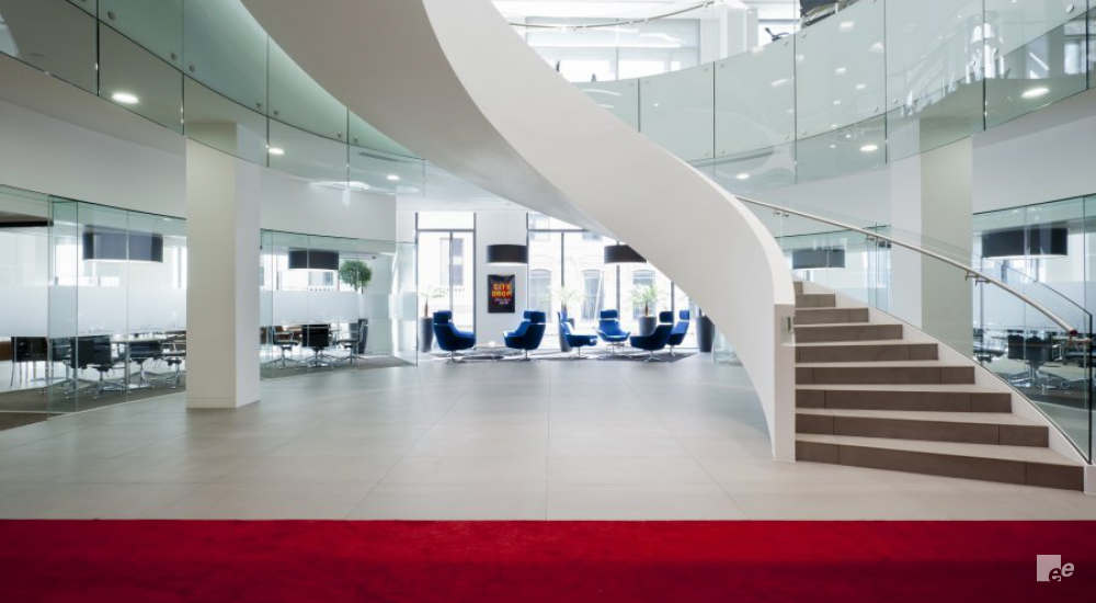 The office of an insurer, with a winding staircase in the hall, red carpet, fauteuils and lamps
