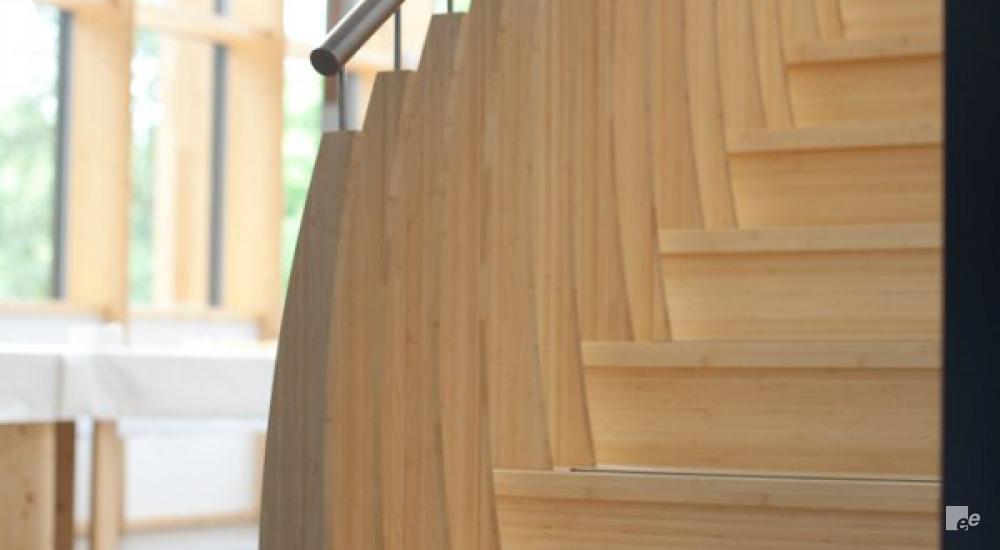 A close-up of a bamboo staircase with stainless steel handrail. The windows with wooden frames are also visible.