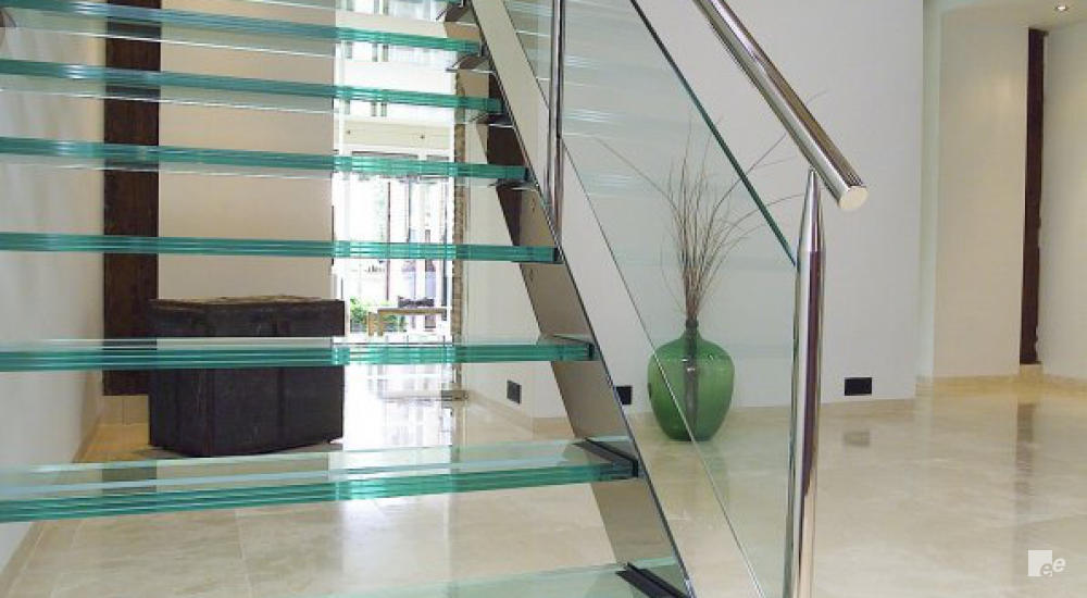 An open glass stairway on a marble floor in a hall with wooden beams and a plant pot.