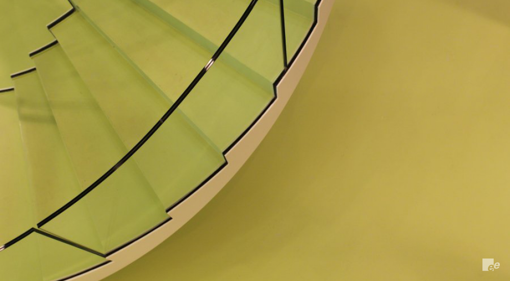 A part of a winding staircase with green painted treads and glass balustrade, above a cast floor.