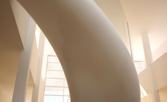 The underside of a winding staircase with EeSoffit finish, in a hall with a glass façade.