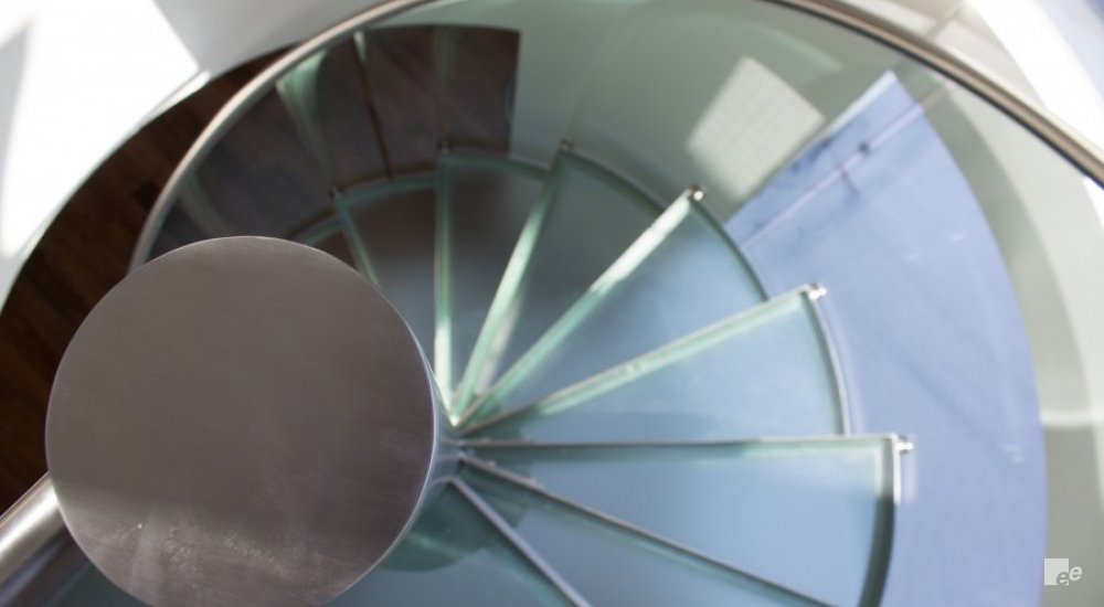 The top side of a stainless steel pivot, with frosted glass treads and a balustrade with stainless steel railing around it.