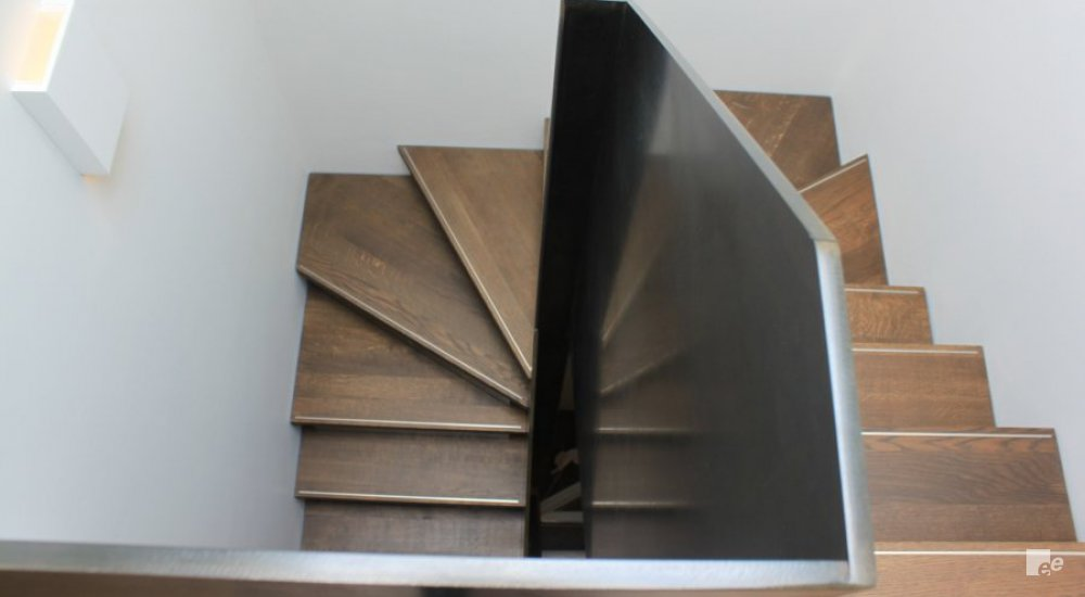 View of a wooden staircase and a balustrade with the Hot Rolled Satin Polish finish by EeStairs.