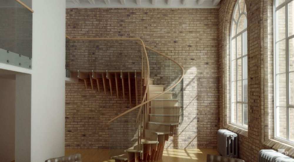 Two leather chairs in a room with arched window, an open staircase, wooden floor and brick walls.