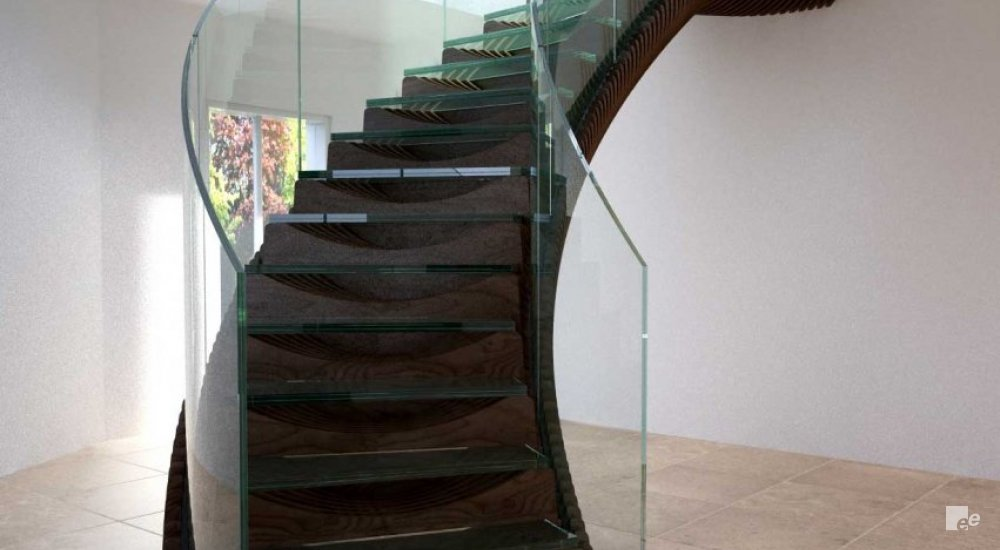 A winding staircase with treads of dark stained wood and glass balustrades in a residence in Ireland.