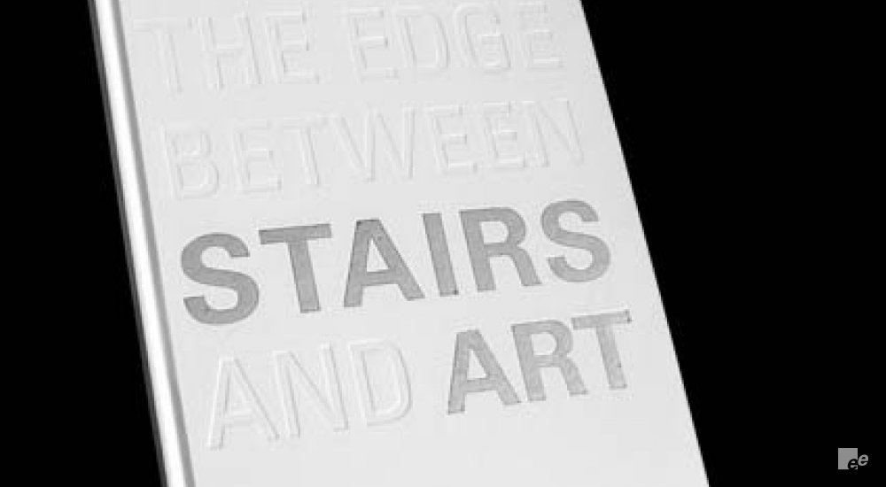 A white cover with embossed letters that form the text 'Explore the edge between stairs and art'.