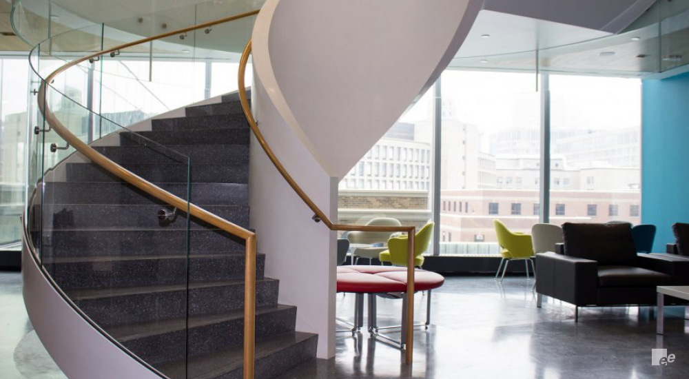 A winding staircase, table with fabric cover, ball chairs and a leather fauteuil in the offices of OICR.