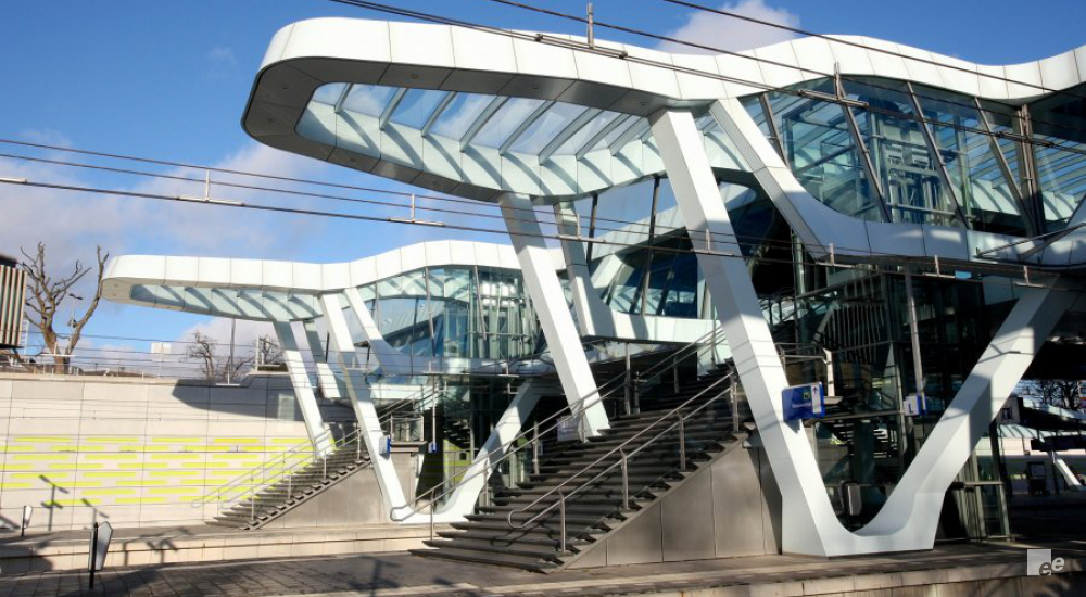 Two staircases near a train station with overarching roofs of glass.