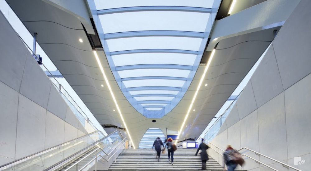 A wide staircase in a modern, grey environment that people are ascending.