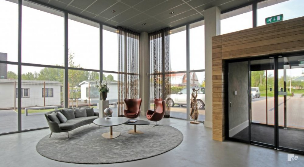 Entrance of tax consultancy bureau LIMES with glass facade, and inside a round rug, sofa, table and armchairs, figurine and a plant.
