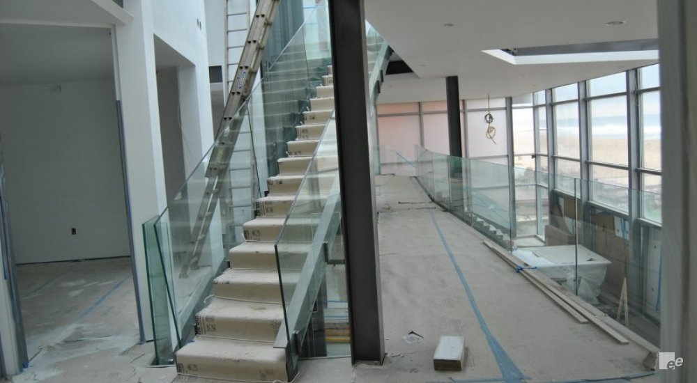 Taped stairs, stuccoed ceiling, a ladder stands against one of the stuccoed walls, glass railings.