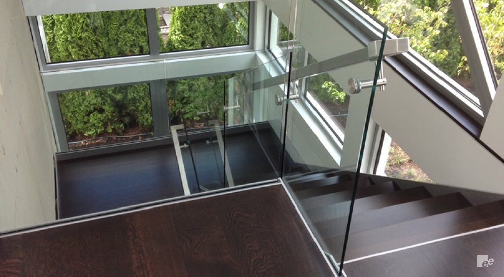 Top view from a wooden floor onto wooden stairs with glass balustrade and stainless steel handrails.