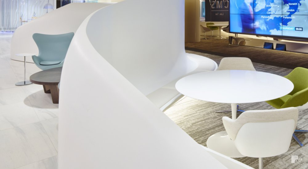 Office chairs and round tables, with a curved white wall as a partition, and a large screen depicting the weather.