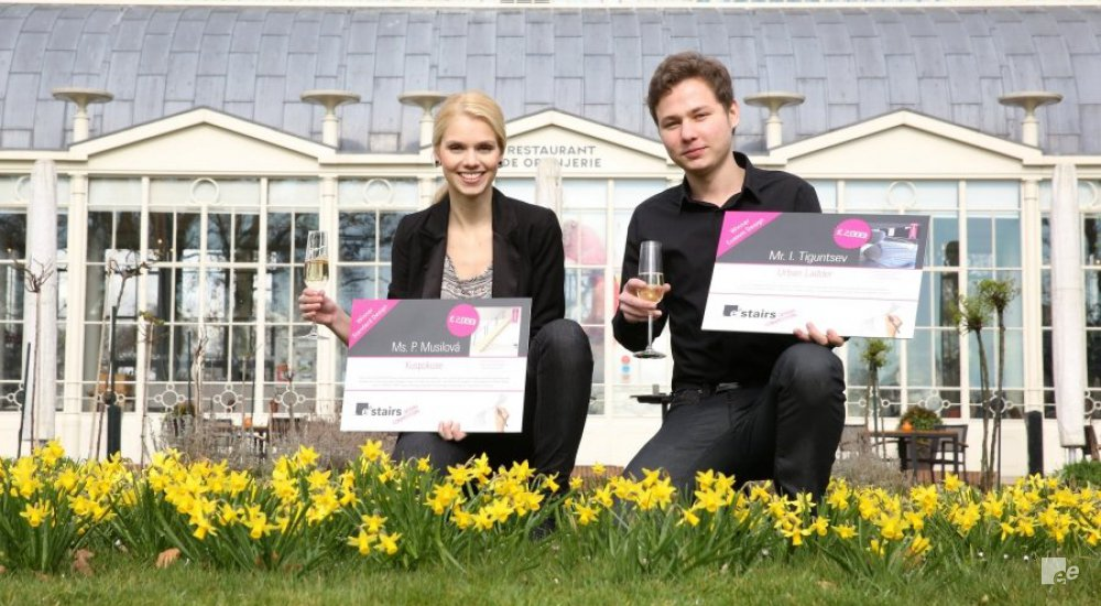 Petra Musilová and Iury Tiguntsev pose with their prize and champagne on a grassy field with narcissus.