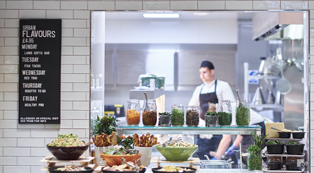 A kitchen with chefs and tools, with different herbs in jars in front of the window.